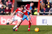 Doncaster Rovers defender Tom Anderson (12) is fouled in the middle of the park during the EFL Sky Bet League 1 match between Scunthorpe United and Doncaster Rovers at Glanford Park, Scunthorpe, England on 23 February 2019.