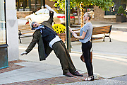 A street performer appears to fall backwards for a tourist in Asheville, North Carolina.
