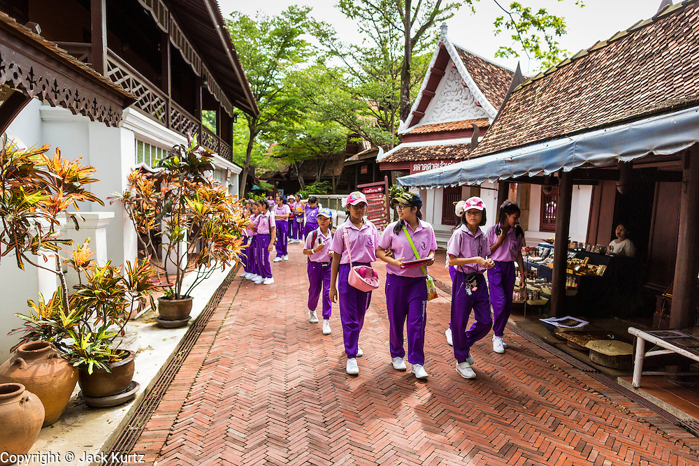 16 JULY 2014 - SAMUT PRAKAN, SAMUT PRAKAN, THAILAND: Thai school children on a field trip wander through the Market Village in Ancient Siam. Ancient Siam is a historic park about 200 acres (81 hectares) in size in the city of Samut Prakan, province of Samut Prakan, about 90 minutes from Bangkok. It features historic recreations of important Thai landmarks and is shaped roughly like the country of Thailand.      PHOTO BY JACK KURTZ