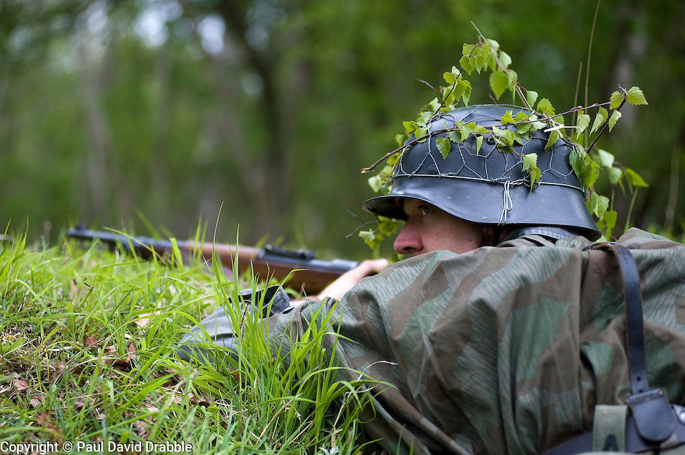 Reenactor from Northern World War Two Association, dressed as Panzer Grenadier from the Elite Grossdeutschland Division armed with a Mauser K98 and wearing the iconic coal scuttle helmet (stahlhelm) with splinter pattern camouflage zeltbahn  during a private 24hr exercise, held at Sutton Grange, near Ripon in Yorkshire. <br />