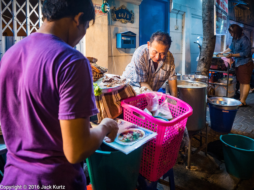 17 JANUARY 2016 - BANGKOK, THAILAND: A man looks at the menu of a noodle shop while the owner (right) prepares an order on Sukhumvit Soi 38, one of the most famous street food areas in Bangkok. The food carts and small restaurants along the street have been popular with tourists and Thais alike for more than 40 years. The family that owns the land along the soi recently decided to sell to a condominium developer and not renew the restaurant owners' leases. More than 40 restaurants and food carts will have to close. Most of the restaurants on the street closed during the summer of 2015. The remaining restaurants are supposed to close by the end of this week.           PHOTO BY JACK KURTZ