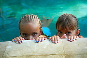 Two Australian children tourists (9 years old and 6 years old) peering over edge of swimming pool, with braided hair and painted fingernails. Bali, Indonesia.