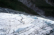 People walking on glacial ice embedded with moraine sediment transported by Fox glacier, New Zealand