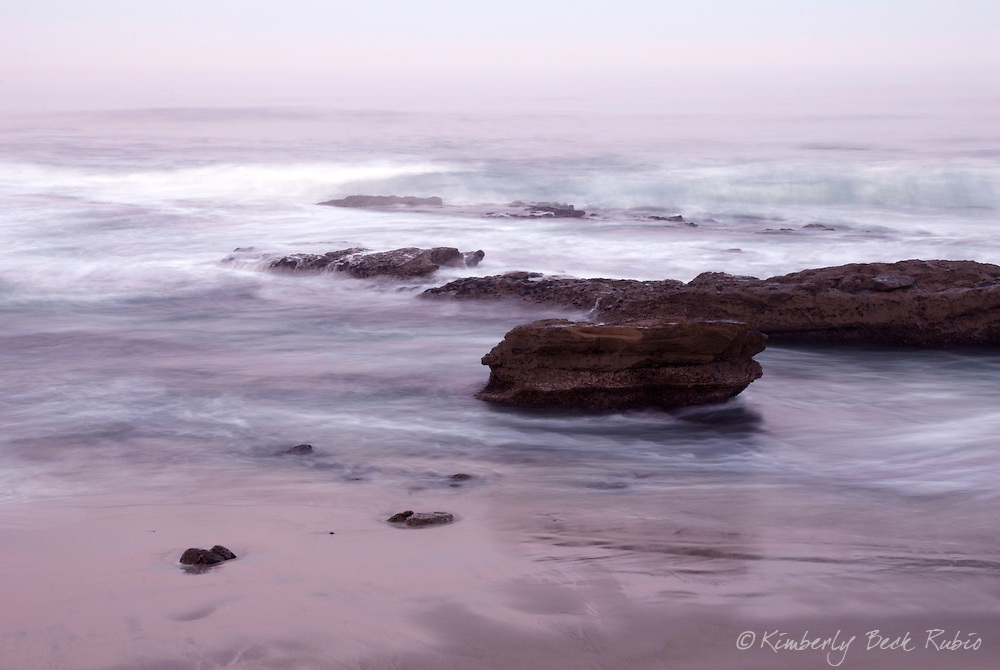 Early morning pink hues reflect in the water before sunrise at La Jolla Cove in La Jolla, California.