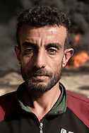 Iraq, Qayyara: On October 2016, Youssef Sadi Latif gestures that after IS left the village of Qayyara he is free to smoke.<br /> He even underlined as for IS was forbidden to smoke but not to set on fire the crude oil field behind him. Alessio Romenzi