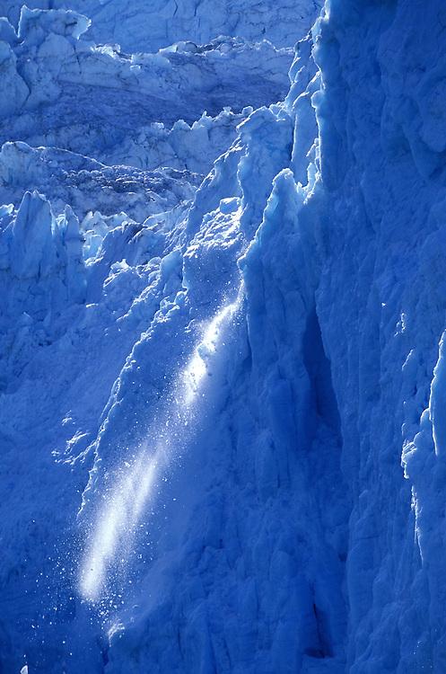 USA, Alaska, Kenai Fjords National Park, Icebergs and snow falls from sheer face of Aialik Glacier during midsummer