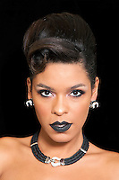 Gorgeous woman with black lipstick posing against black background