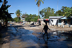 A woman walks through a street showing some remnants of flooding left over from Hurricane Sandy. Hurricane Sandy brought heavy flooding to the region , destroyed crops and livestock and will seriously hinder farmers' abilities to grow food in the future.