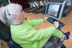 Older woman watching TV screen whilst working out on exercise bikes at a gym,