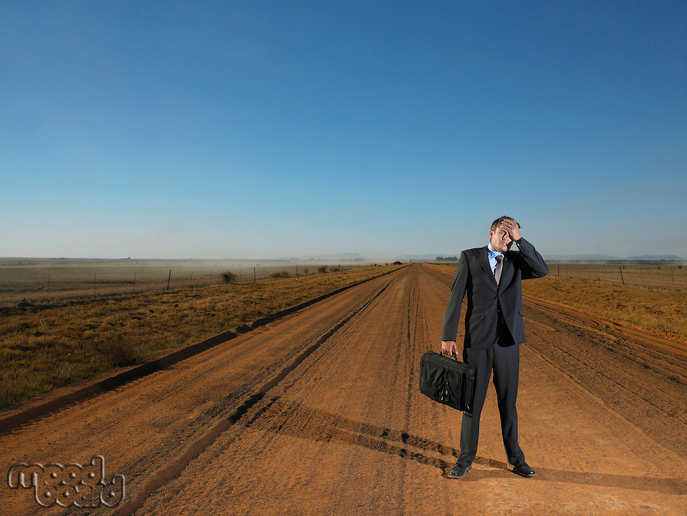 Businessman standing in road holding his head