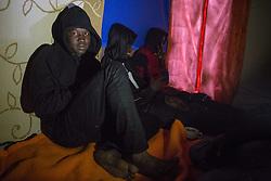 """Calais, Pas-de-Calais, France - 16.10.2016    <br />     <br />  Sudanese refugees inside their booth in the """"Jungle"""" camp on the outskirts of the French city of Calais. Many thousands of migrants and refugees are waiting in some cases for years in the port city in the hope of being able to cross the English Channel to Britain. French authorities announced that they will shortly evict the camp where currently up to up to 10,000 people live.<br /> <br /> Sudanesische Fluechtlinge in ihrer selbstgebauten Huette im """"Jungle"""" Camp am Rande der franzoesischen Stadt Calais. Viele tausend Migranten und Fluechtlinge harren teilweise seit Jahren in der Hafenstadt aus in der Hoffnung den Aermelkanal nach Großbritannien ueberqueren zu koennen. Die franzoesischen Behoerden kuendigten an, dass sie das Camp, indem derzeit bis zu bis zu 10.000 Menschen leben Kürze raeumen werden. <br /> <br /> Photo: Bjoern Kietzmann"""