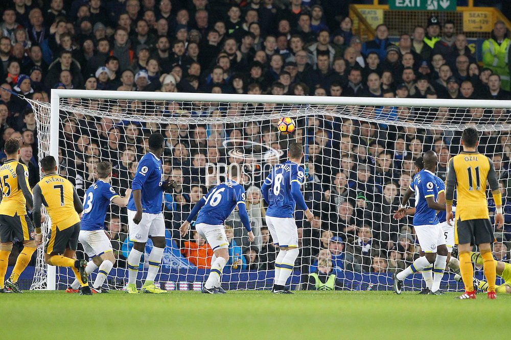 Arsenal's Alexis Sanchez (7) watches his free kick clear the wall to open the scoring 0-1 during the Premier League match between Everton and Arsenal at Goodison Park, Liverpool, England on 13 December 2016. Photo by Craig Galloway.