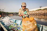 Pak Ahya (52) gathers plastic bottles and scraps that he found floating on the Citarum River. Citeureup Village, Kabupaten Bandung...Credit: Andri Tambunan for Greenpeace