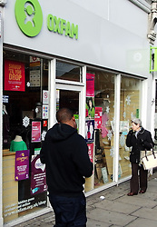 "Pedestrians walk past an Oxfam charity shop in Edgware, North London, England, after it had been announced that Oxfam is set to cut 125 posts in the UK and close several of its regional offices to make it more ""efficient"", the charity has said.Its headquarters in Oxford will be most affected, with 110 jobs being axed, Friday, 25th October 2013. Picture by Max Nash / i-Images"