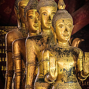 A line of four Buddha statues at Wat Mai Suwannaphumaham.  Wat Mai, as it is often known, is a Buddhist temple in Luang Prabang, Laos, located near the Royal Palace Museum. It was built in the 18th century and is one of the most richly decorated Wats in Luang Prabang.