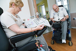 Disabled couple reading together at home,