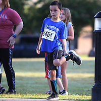 Levi Franks, 7, stretches Saturday morning before participating in the Blessed are the Peacemakers 5k hosted by the Wives of Warriors