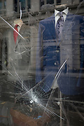 Detail of a damaged shop window selling menswear and suits, on 14th September 2017, in the City of London, England.