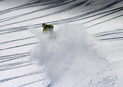 Tim Hoff in an explosion of powder as rips his Skidoo off a cornice in the Snake River range, Wyoming