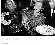Dachshunds fighting over Doggy canapes. Iris Love ( holding Just deserts) & Brooke Astor ( holding Dolly Astor ) at a Dachshund Party. Barbetta. New York. 12 February 1990. Film. 9086/16<br />