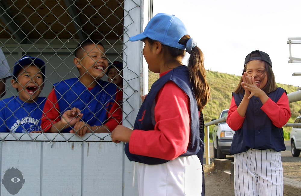 Boys and girls socialize between the fenced dugout during a baseball game on the Warm Springs Indian Reservation in Warm Springs, Oregon. They were making fun of eachother because two of them liked the other.
