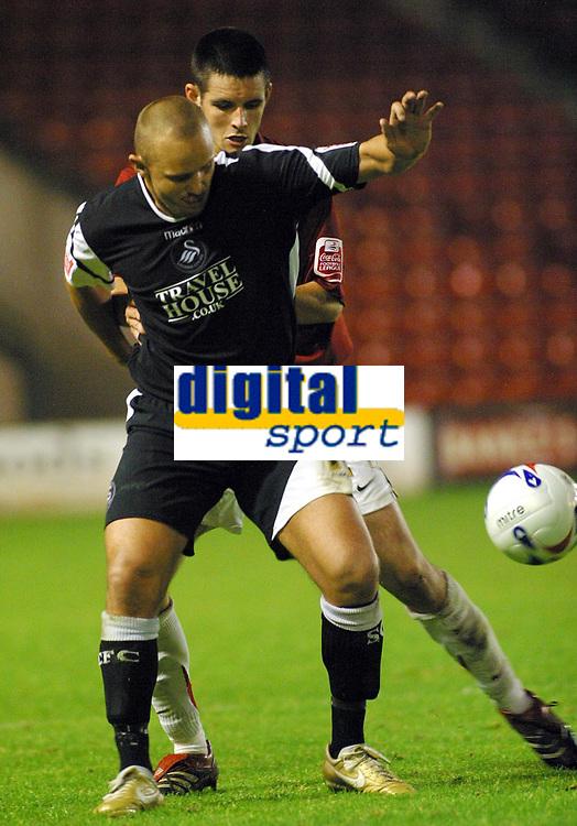 Photo: Dave Linney.<br />Walsall v Swansea City. Johnstone's Paint Trophy. 17/10/2006.Swansea srtriker Lee Trundle(Front) is shadowed by  Scott Dann
