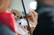 Close-up of violin, bow, bridge, fine tuners and strings being played by female mararchi.