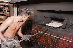 Baker putting bread rolls into oven in bakery; Havana; Cuba,