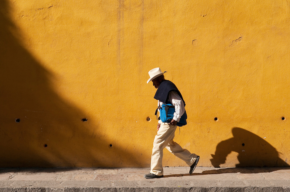 Man walking in front of yellow wall; San Miguel de Allende, Guanajuato, Mexico.