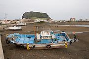 Jeju Island. Seongsan Ilchulbong (Sunrise Peak), starnded fish trawlers during low tide.