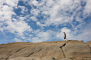 A 13 year-old teenage boy walks along the tops of sandstone rocks in the coastal cove of Trentishoe in north Devon.