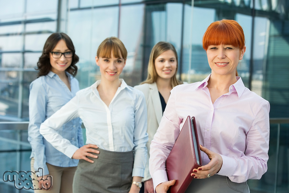 Portrait of confident businesswoman holding folder with female colleagues standing in background