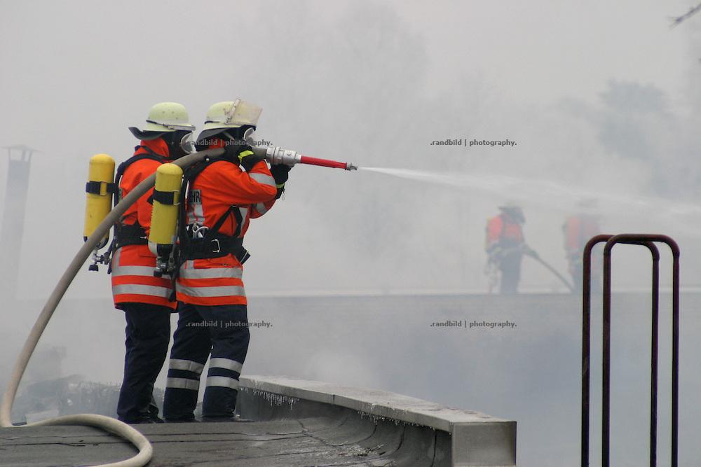 Zwei Feuerwehrmänner versuchen eine Kette an einem brennenden Fabrikhallendach zu befestigen...German Fire Fighters at a burning industrial complex in Dannenberg.