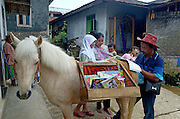 PURBALINGGA, INDONESIA - DECEMBER 02:<br /> <br />  Ridwan Sururi (42 years), along with Luna 'Horse Mobile Library' lend books to students at Serang village on December 02, 2015 in Purbalingga, Central Java, Indonesia. Every Tuesday, Wednesday and Thursday, he walks with his horse mobile library around the villages. Ridwan Sururi initiative horse mobil library, intended to make the public and students to read.<br /> ©Exclusivepix Media