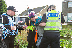 © Licensed to London News Pictures. 10/10/2017. Kirby Misperton UK. An Anti fracking campaigner is restrained by police as the drilling rig arrived at the Kirby Misperton KM8 fracking site this morning despite 22 days of protests & daily attempts to block access to the Kirby Misperton fracking site by anti fracking campaigners. Third Energy was granted planning permission last year to frack the site but has not yet received final consent to begin fracking, but expects to start before the end of the year. Photo credit: Andrew McCaren/LNP