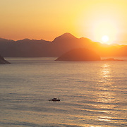 Praia de Copacabana at sunrise. The view from Copacabana beach, one of the world's most famous urban beaches at sunrise. The beach and hotel strip stretches for 1.5 miles (4km) from the Morro do Leme at the Northern end, to Arpoador. Copacabana beach, Rio de Janeiro,  Brazil. 21st July 2010. Photo Tim Clayton..