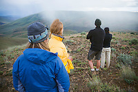Four people (1 man and 3 women) standing on a hillside in the high plains desert watching a rain storm approach...20060527_MR_B.20060527_MR_C.20060527_MR_D.20060527_MR_E