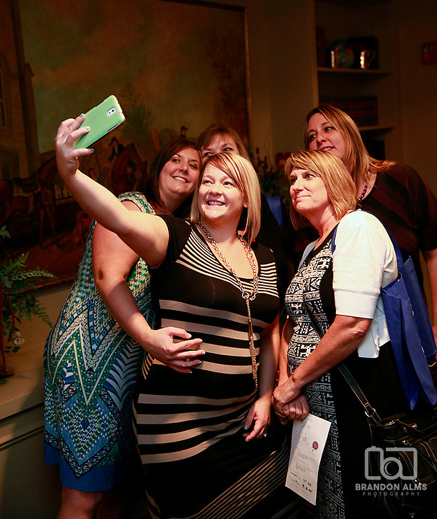 A group of women having fun and taking selfies at a 417 Magazine Event.