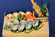 Assortment of Sushi on a wooden platter including: Sushi Maki, futo maki, Insideout and tempura