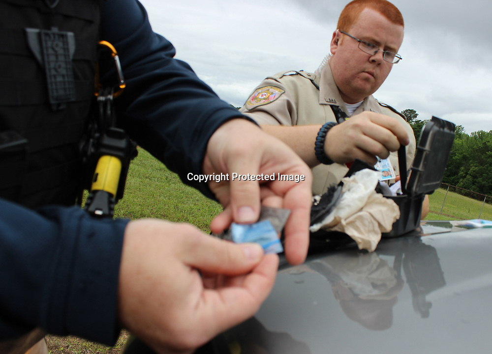 Amory Police Department Investigator Andy Long, left, holds small bags of ICE confiscated following a traffice stop, as Monroe County deputy Cayce Minich searches for more evidence.