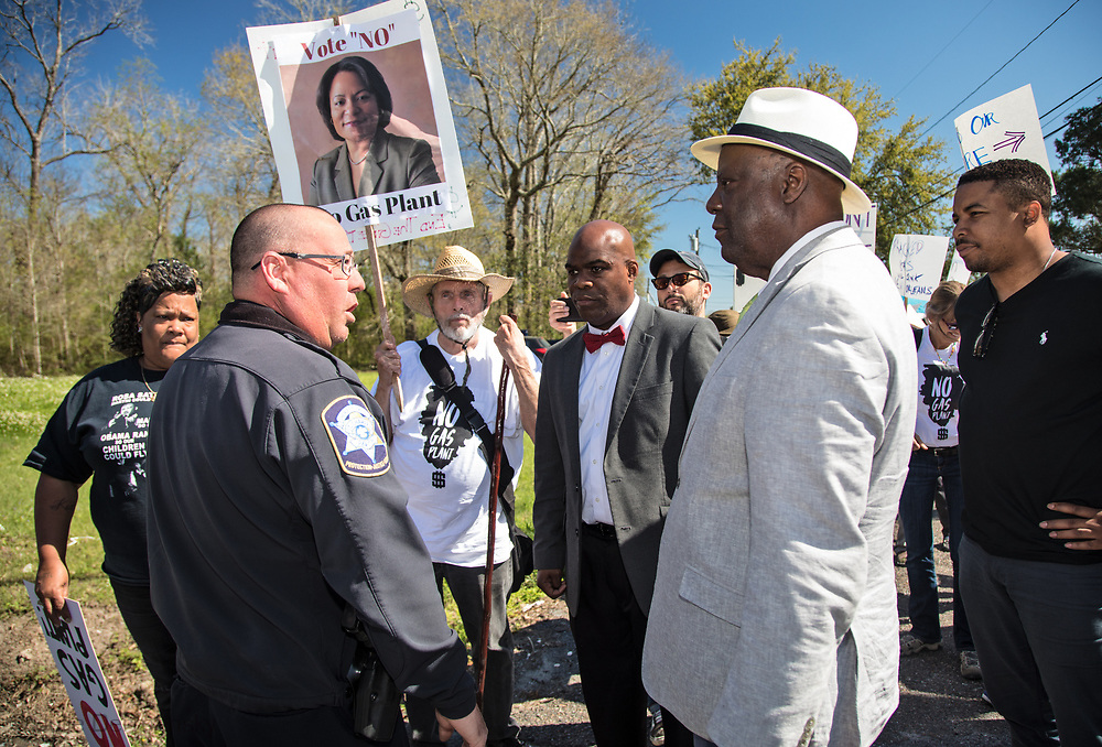 A police office talks to opponents of Entergy's Natural Gas Power plant in New Orleans East before they marched along River Road in Cancer Alley on March 3, 2018.  The march passed Entergy's Waterford 3 Nuclear Generating Station and  Dows Chemical Plant, ending at the Taft Cemetery.