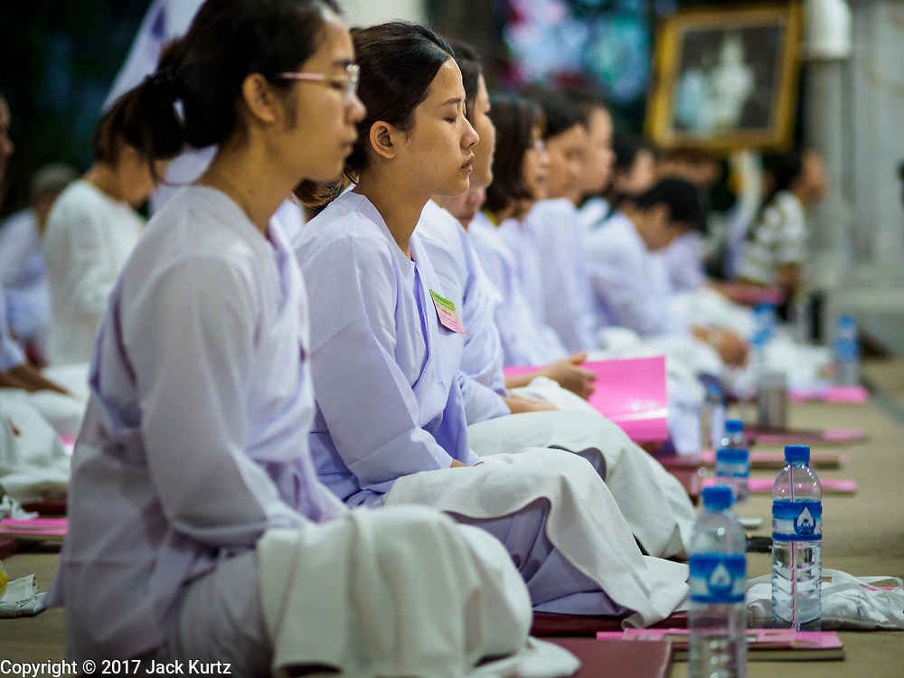 31 DECEMBER 2017 - BANGKOK, THAILAND: Women participate in an overnight meditation session on New Year's Eve at Wat Pathum Wanaram in central Bangkok. Many Thais go to temples and shrines to pray and meditate during New Year's Eve and New Year's Day.    PHOTO BY JACK KURTZ