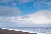 Shoreline and shingle pebble beach with blue sky and puffy clouds in wintertime at Cley Next The Sea, Norfolk, UK