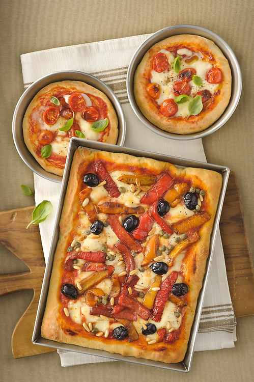 two margherita and one tomato and pepper pizzas in baking tin