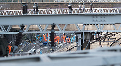 © Licensed to London News Pictures. 25/08/2017. London, UK. Workmen next to the tracks at Euston station in London, which is due to close over the bank holiday weekend for upgrade work at the station in preparation for HS2..  Road and rail services are being affected by maintenance work this weekend - one of the busiest in the year. Photo credit: Ben Cawthra/LNP