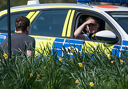 © Licensed to London News Pictures. 07/04/2020. London, UK. Police in a patrol car moving a man who is sitting in Queens Park, north west London, during a pandemic outbreak of the Coronavirus COVID-19 disease. The public have been told they can only leave their homes when absolutely essential, in an attempt to fight the spread of coronavirus COVID-19 disease. Photo credit: LNP