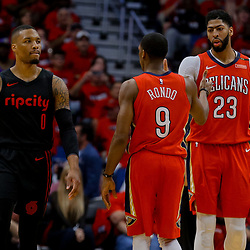 Apr 19, 2018; New Orleans, LA, USA; Portland Trail Blazers guard Damian Lillard (0) looks to the bench as New Orleans Pelicans forward Anthony Davis (23) and guard Rajon Rondo (9) celebrate a basket during the second half in game three of the first round of the 2018 NBA Playoffs at the Smoothie King Center. The Pelicans defeated the Trail Blazers 119-102.  Mandatory Credit: Derick E. Hingle-USA TODAY Sports
