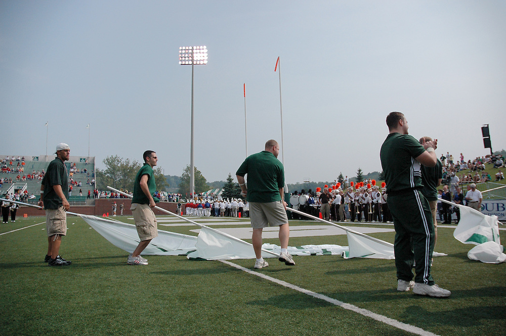 Some alumni cheerleaders get ready to run out with the team, carrying the O,H,I,O Flags
