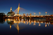 Skyline of the City of Winnipeg reflected in the Red River featuring the Canadian Museum for Human Rights (CMHR) and the Esplanade Riel Bridge at dusk<br /> Winnipeg<br /> Manitoba<br /> Canada