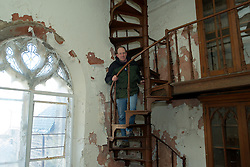 Weinstein climbs the cast iron staircase in the library. (Bas Slabbers/for NewsWorks)